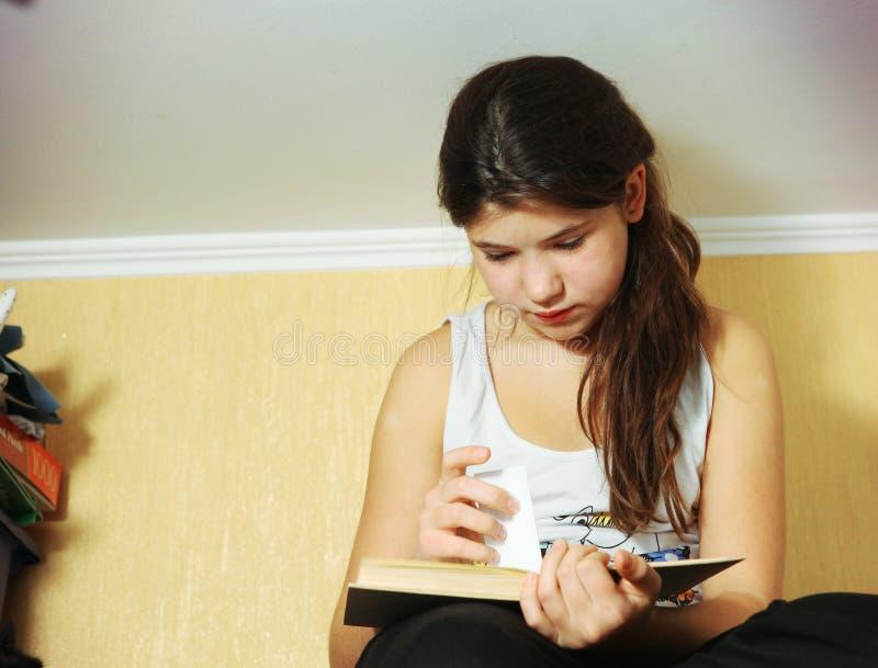 碗柜的青春期前的美丽的女孩读了书 免版税图库摄影
