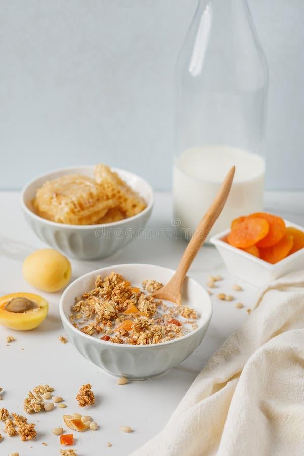 碗格兰诺拉麦片用在白色桌上的杏干 木匙子 免版税库存图片