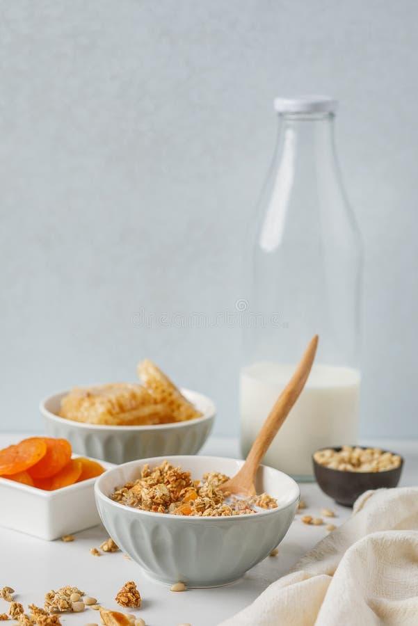 碗格兰诺拉麦片用在白色桌上的杏干 木匙子 库存图片