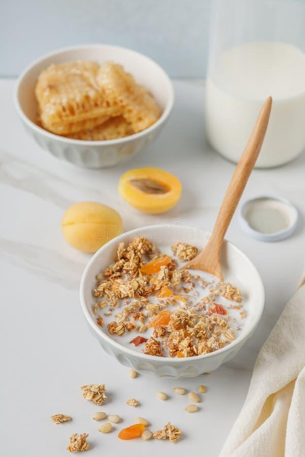 碗格兰诺拉麦片用在白色桌上的杏干 木匙子 免版税图库摄影