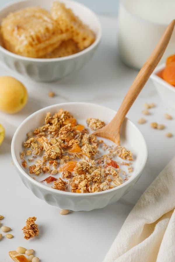 碗格兰诺拉麦片用在白色桌上的杏干 木匙子 免版税库存照片