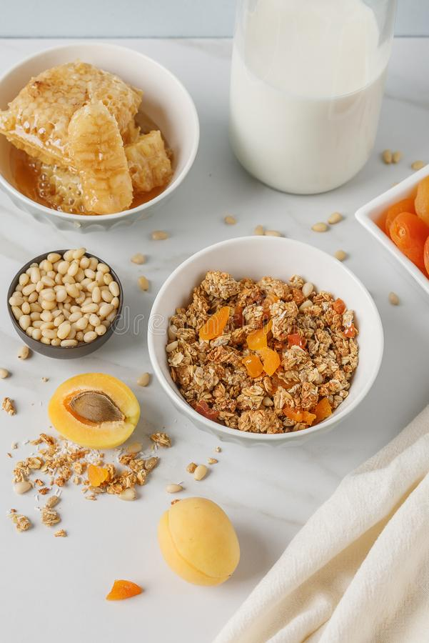碗格兰诺拉麦片用在白色桌上的杏干 木匙子 库存照片