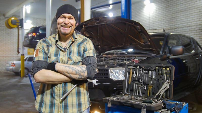 碗汽车推力增强的油替换服务 坚持汽车和咧嘴的残酷技工人 免版税库存图片