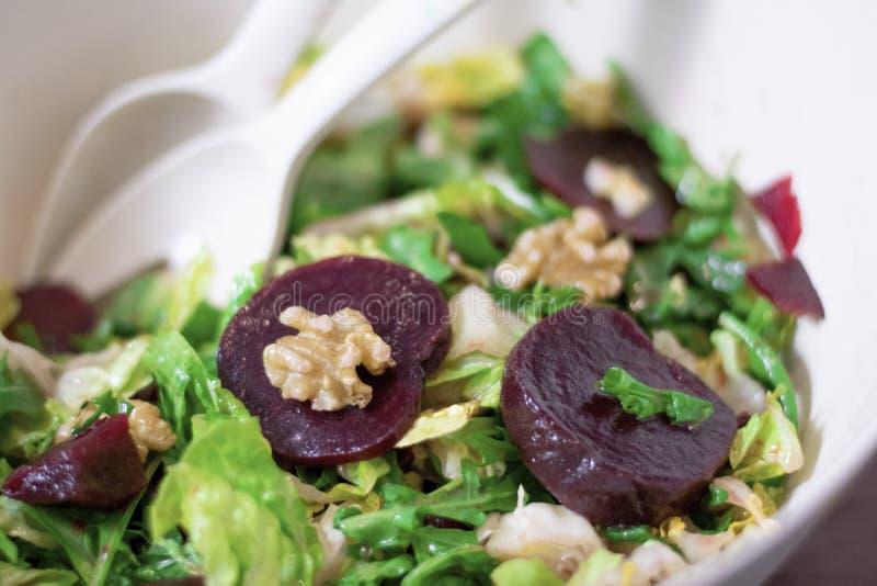 碗甜菜或甜菜根、核桃和莴苣在一张木桌上 库存图片