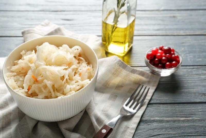 碗用可口德国泡菜和蔓越桔在木桌上 免版税库存图片