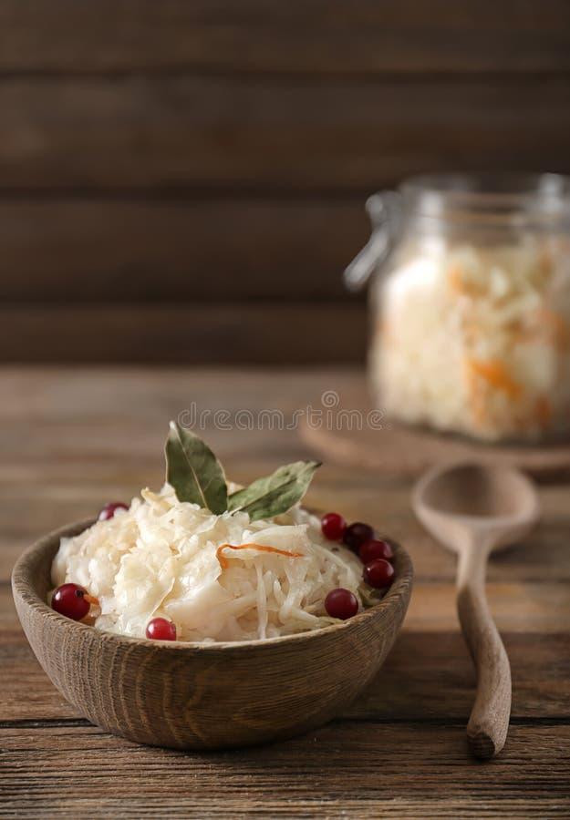 碗用可口德国泡菜和蔓越桔在木桌上 图库摄影