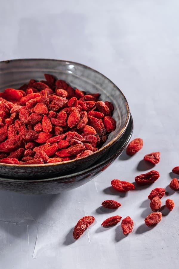 碗用在浅灰色的背景的红色干goji莓果与拷贝空间 免版税库存照片