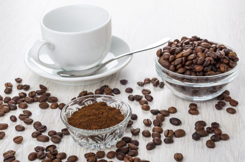 碗用碾碎的咖啡,咖啡豆,空的杯子,匙子 免版税库存照片