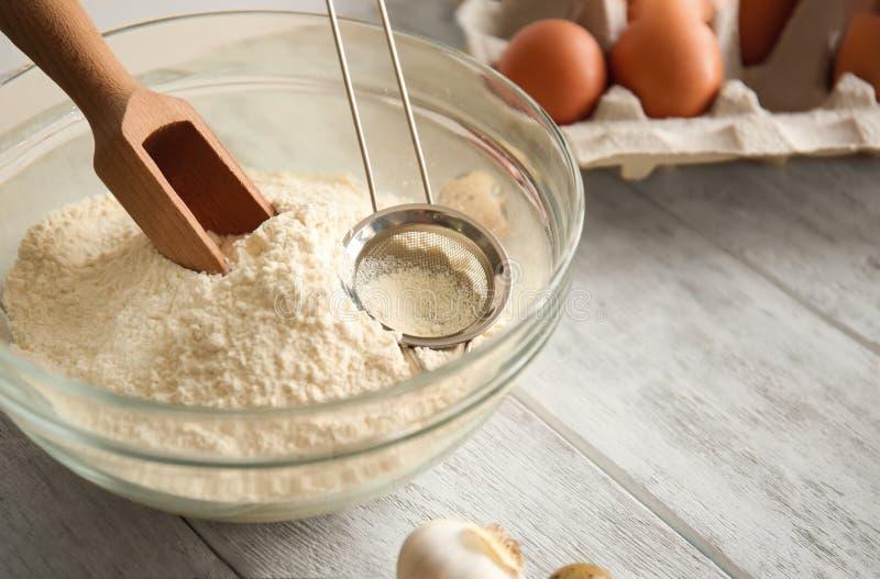 碗用面粉、瓢和筛子在桌上 面包店车间 免版税库存图片