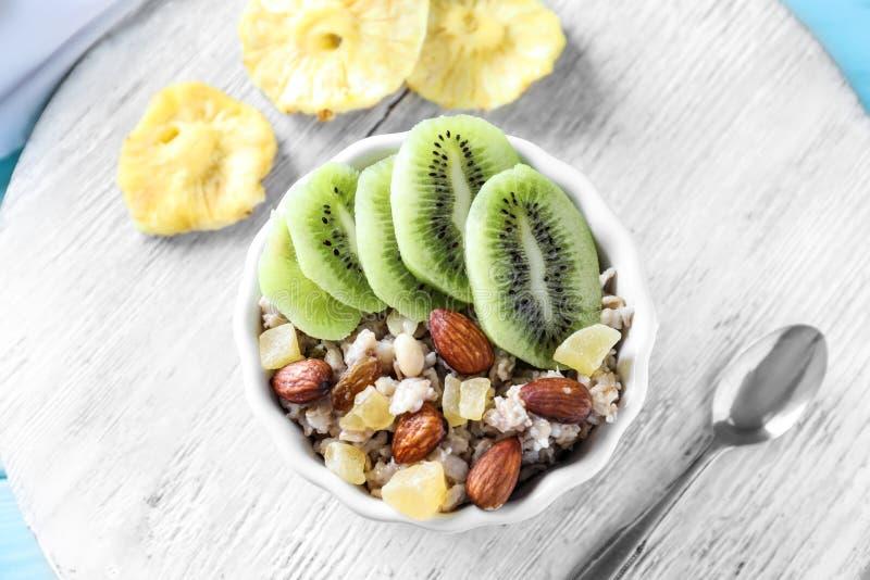 碗用鲜美燕麦粥、杏仁、被切的猕猴桃和脯在木桌上 免版税库存图片