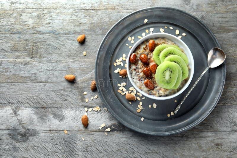 碗用鲜美燕麦粥、被切的猕猴桃和坚果在木桌上 库存图片