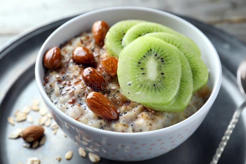 碗用鲜美燕麦粥、被切的猕猴桃和坚果在桌,特写镜头上 免版税图库摄影