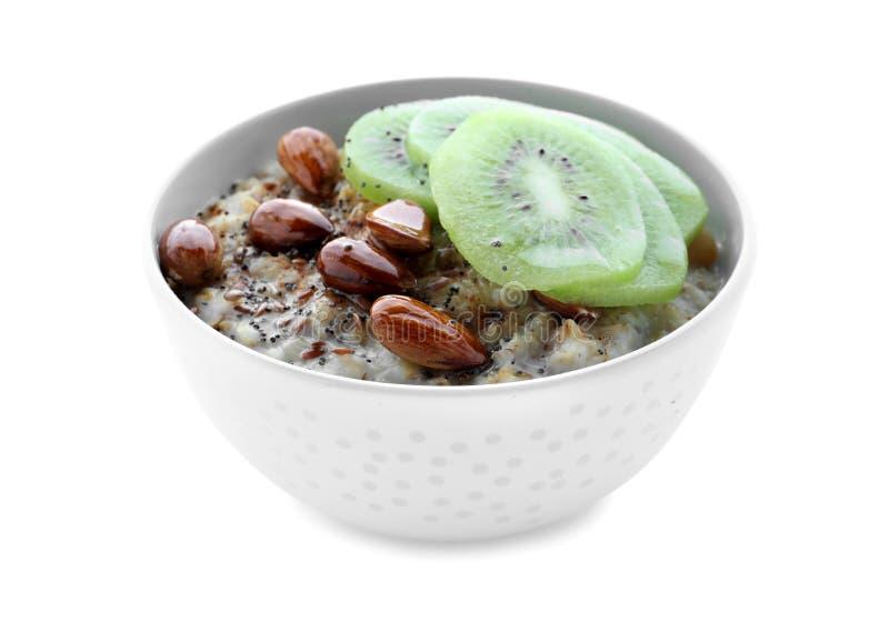 碗用鲜美燕麦粥、被切的猕猴桃和坚果在白色背景 免版税库存图片