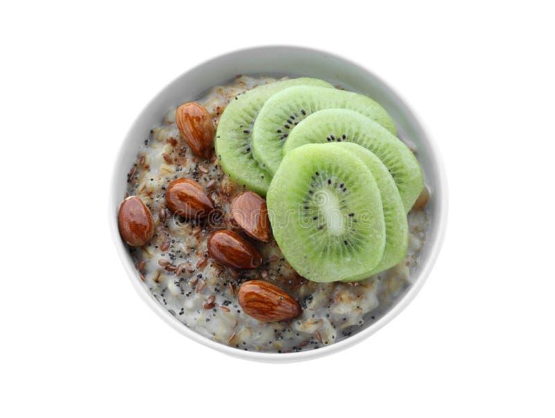 碗用鲜美燕麦粥、被切的猕猴桃和坚果在白色背景 图库摄影