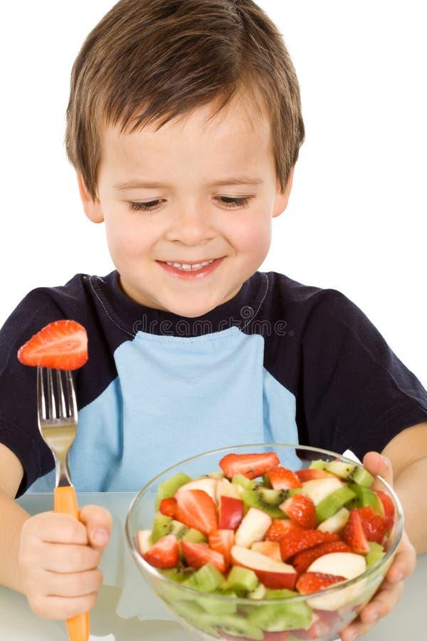 碗男孩吃新鲜水果大沙拉 免版税图库摄影