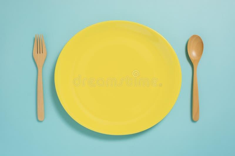 碗筷、黄色板材和叉子平的位置在淡色蓝色colo 图库摄影