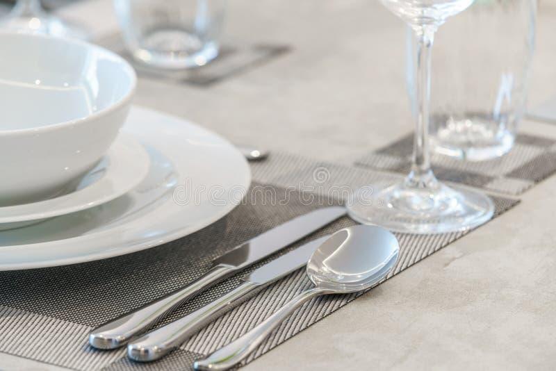 碗筷和餐巾在桌上 免版税库存图片