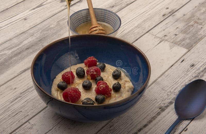碗粥用莓、蓝莓和下毛毛雨的蜂蜜 免版税库存图片