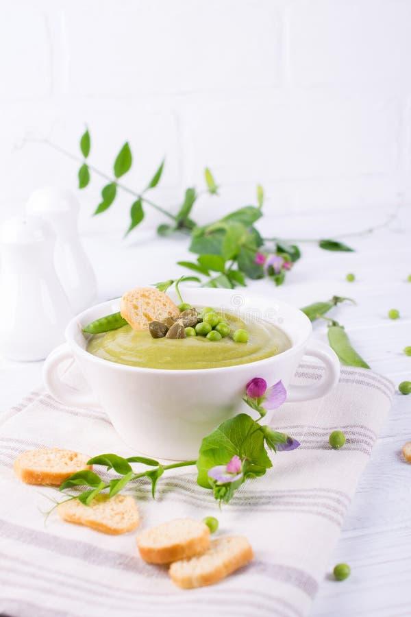 碗自创绿色春天浓豌豆汤冠上了与南瓜籽,油煎方型小面包片 在白色 库存图片