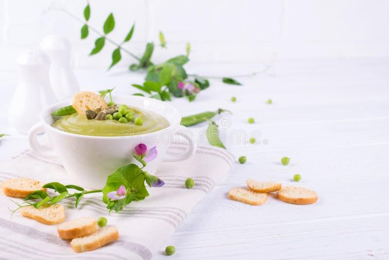 碗自创绿色春天浓豌豆汤冠上了与南瓜籽,油煎方型小面包片 在空白背景 库存图片