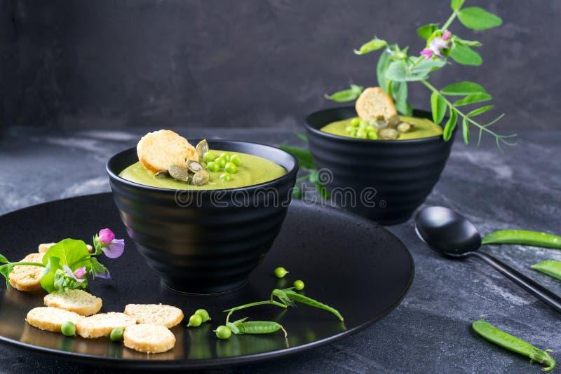 碗自创绿色春天浓豌豆汤冠上了与南瓜籽,油煎方型小面包片 在黑暗的石头 库存图片