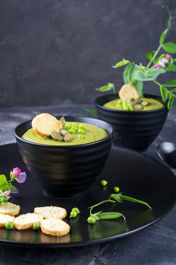 碗自创绿色春天浓豌豆汤冠上了与南瓜籽,油煎方型小面包片 在黑暗的石头 免版税库存图片