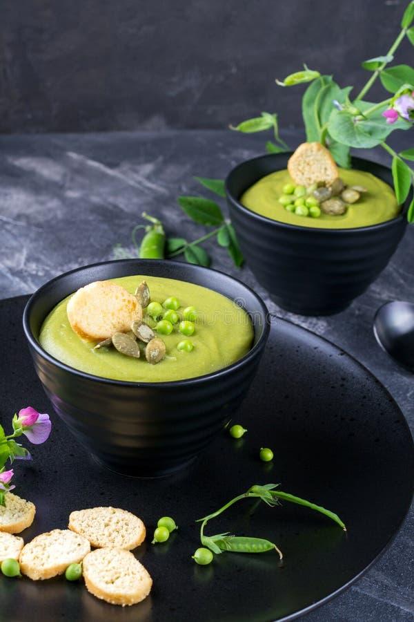 碗自创绿色春天浓豌豆汤冠上了与南瓜籽,油煎方型小面包片 在黑暗的石头 库存照片