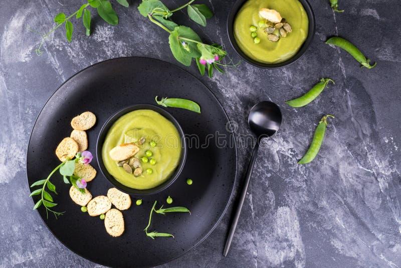 碗自创绿色春天浓豌豆汤冠上了与南瓜籽,油煎方型小面包片 在黑暗的石背景 图库摄影