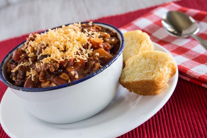 碗辣椒舒适食物用水平玉米面面包的松饼 库存图片