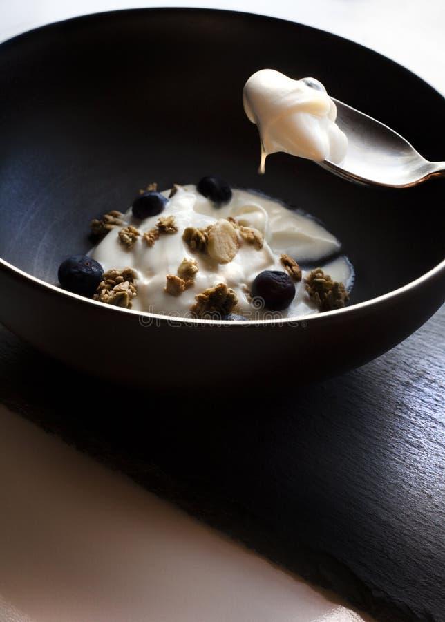 碗酸奶、格兰诺拉麦片和蓝莓 免版税库存照片