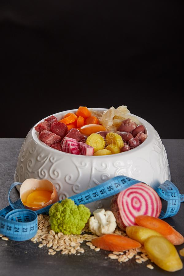 碗barf反对黑背景的食物混合 库存图片