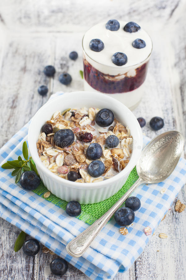 碗muesli用新鲜的蓝莓和杯在whi的酸奶 库存照片