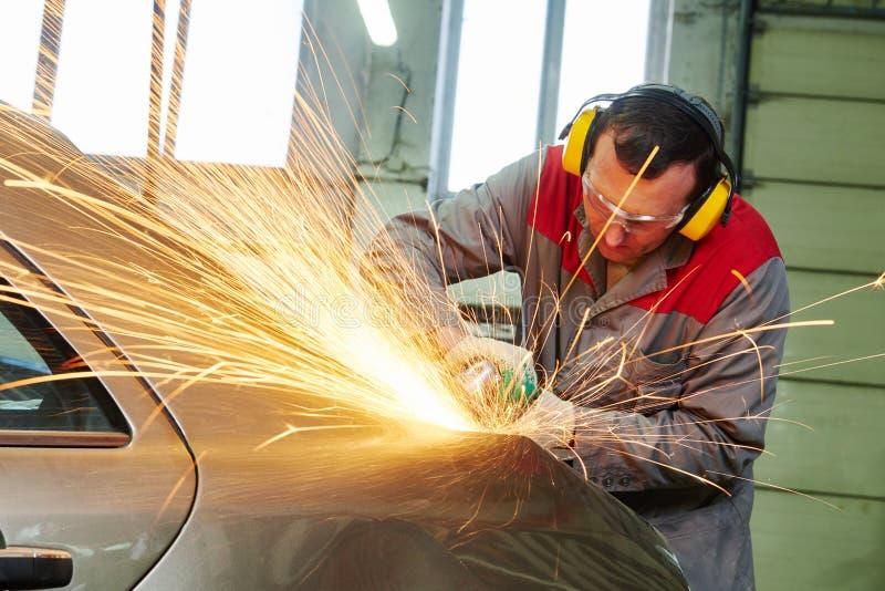 碰撞修理公司 由研磨机的技工研的车身 库存图片