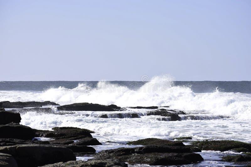 碰撞入岩石水池的波浪作为浪潮进来, Uvongo,南非 免版税库存图片