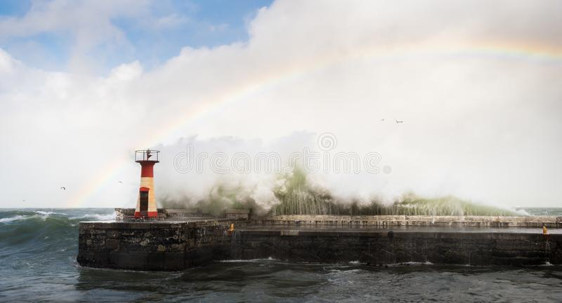 碰撞反对灯塔的巨型的波浪在与一条彩虹的一场风暴期间在天空 免版税库存照片
