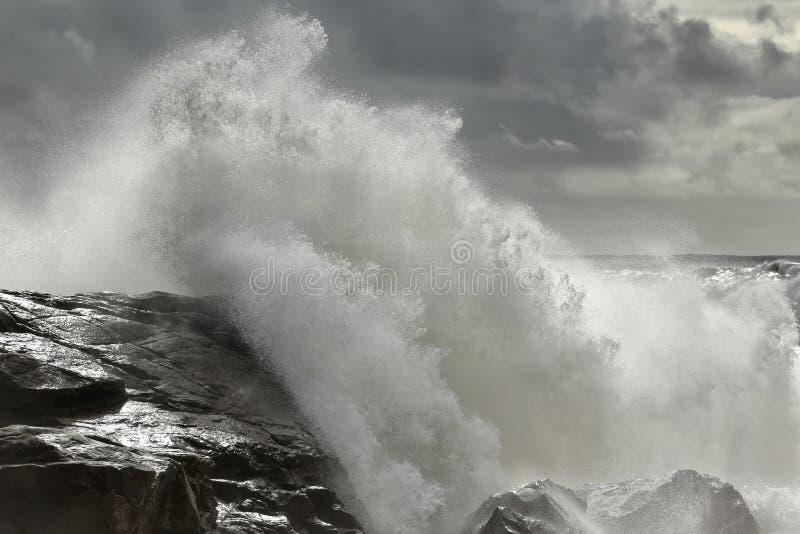 碰撞在岩石海岸的风雨如磐的波浪 免版税库存图片