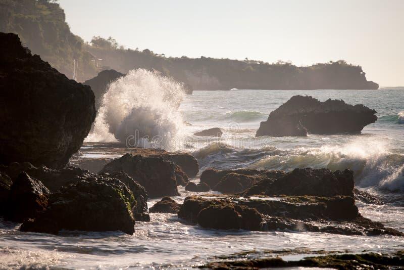 碰撞在日落的岩石上的海浪 库存图片