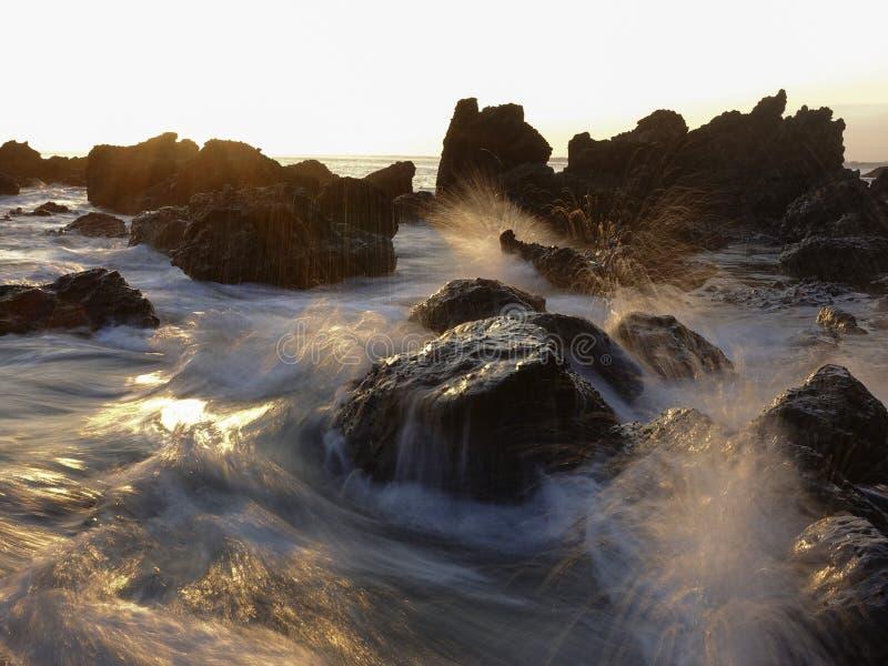 碰撞在海滩的波浪岩石在日落日出 免版税图库摄影