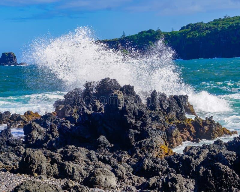 碰撞在熔岩岩石的波浪 免版税库存照片
