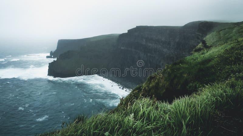 碰撞在莫赫悬崖的波浪,在一有薄雾的天在爱尔兰 免版税库存图片