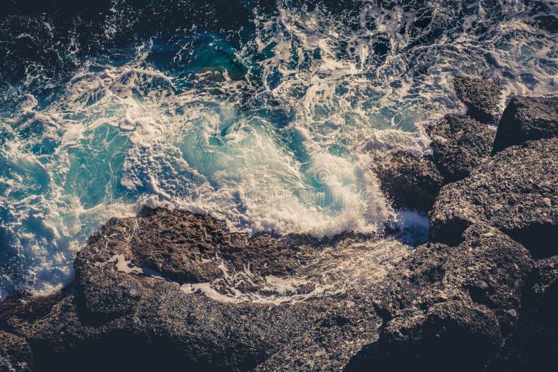 碰撞打破在岩石的波浪 寄生虫空中海表面视图 免版税库存图片