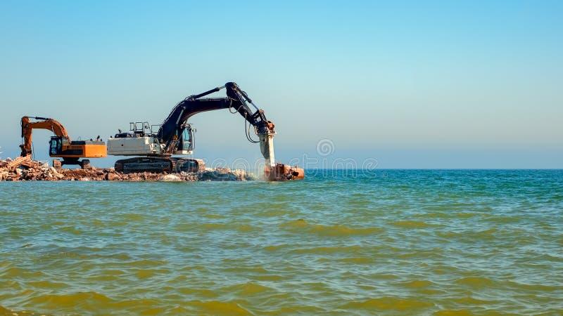 碰撞混凝土的挖掘机入海 免版税库存照片