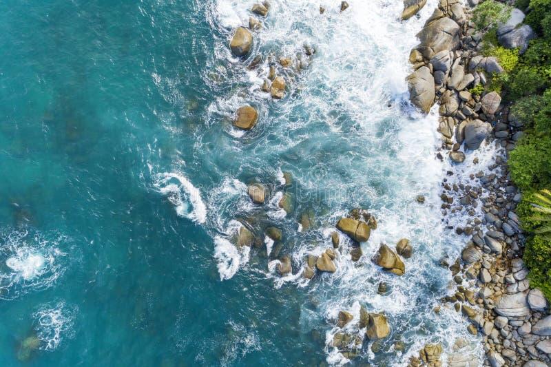 碰撞的波浪鸟瞰图在岩石的使自然视图和美丽的热带海环境美化有沿海视图在夏季图象 库存图片