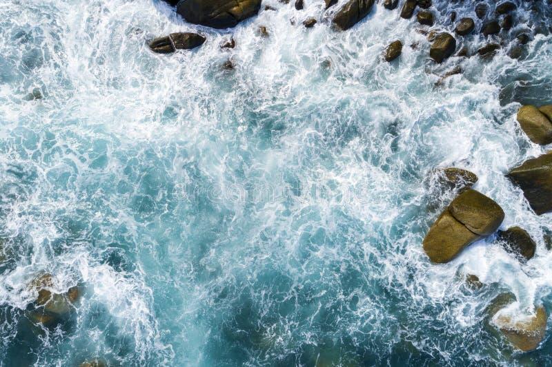 碰撞的波浪鸟瞰图在岩石的使自然视图和美丽的热带海环境美化有沿海视图在夏季图象 免版税图库摄影