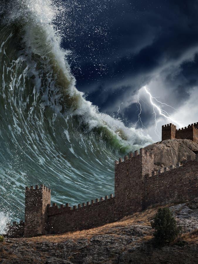碰撞老堡垒的巨型海啸波浪 免版税库存图片