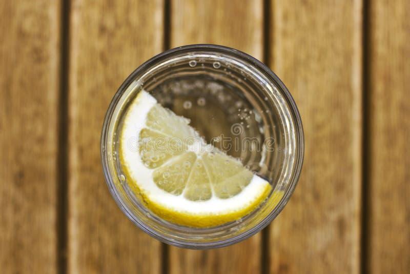 碳酸化合的苏打水用在一块玻璃的柠檬与在增殖比的泡影 免版税图库摄影