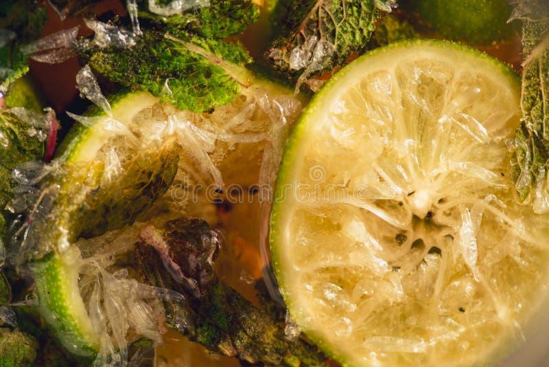 碳酸化合的苏打水或汁液与石灰和薄菏在一个玻璃水罐 宏观特写镜头 库存照片