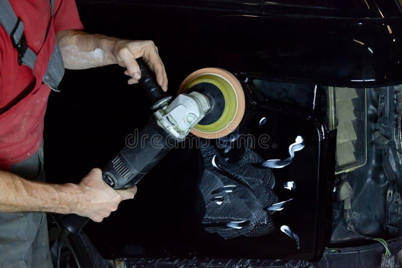 磨光器盖车尸体以特别蜡保护汽车免受较小抓痕和损伤,并且它擦亮 免版税库存照片