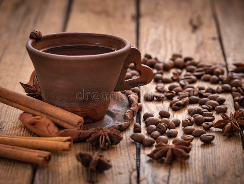 磨咖啡器和热的咖啡在木桌上的 库存图片