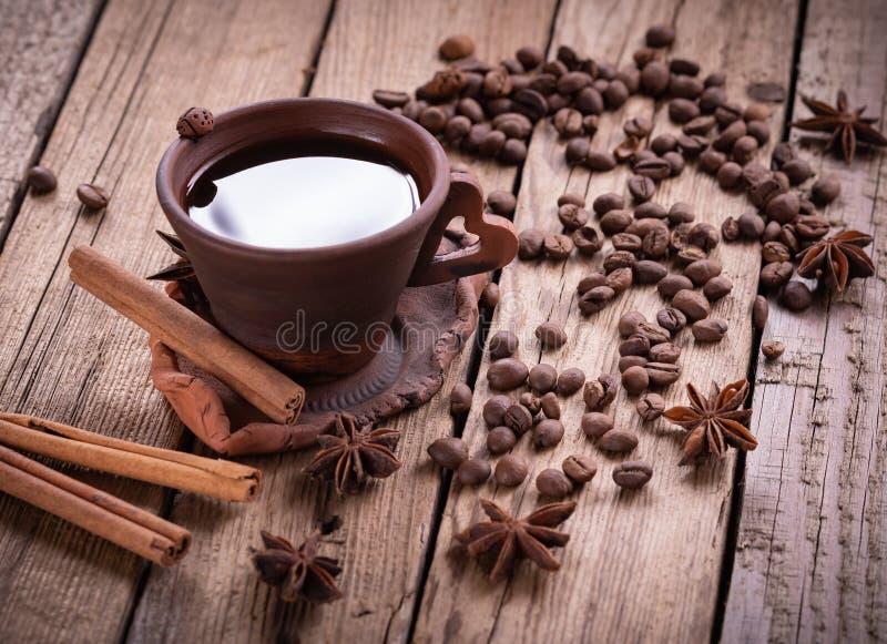 磨咖啡器和热的咖啡在木桌上的 免版税库存图片